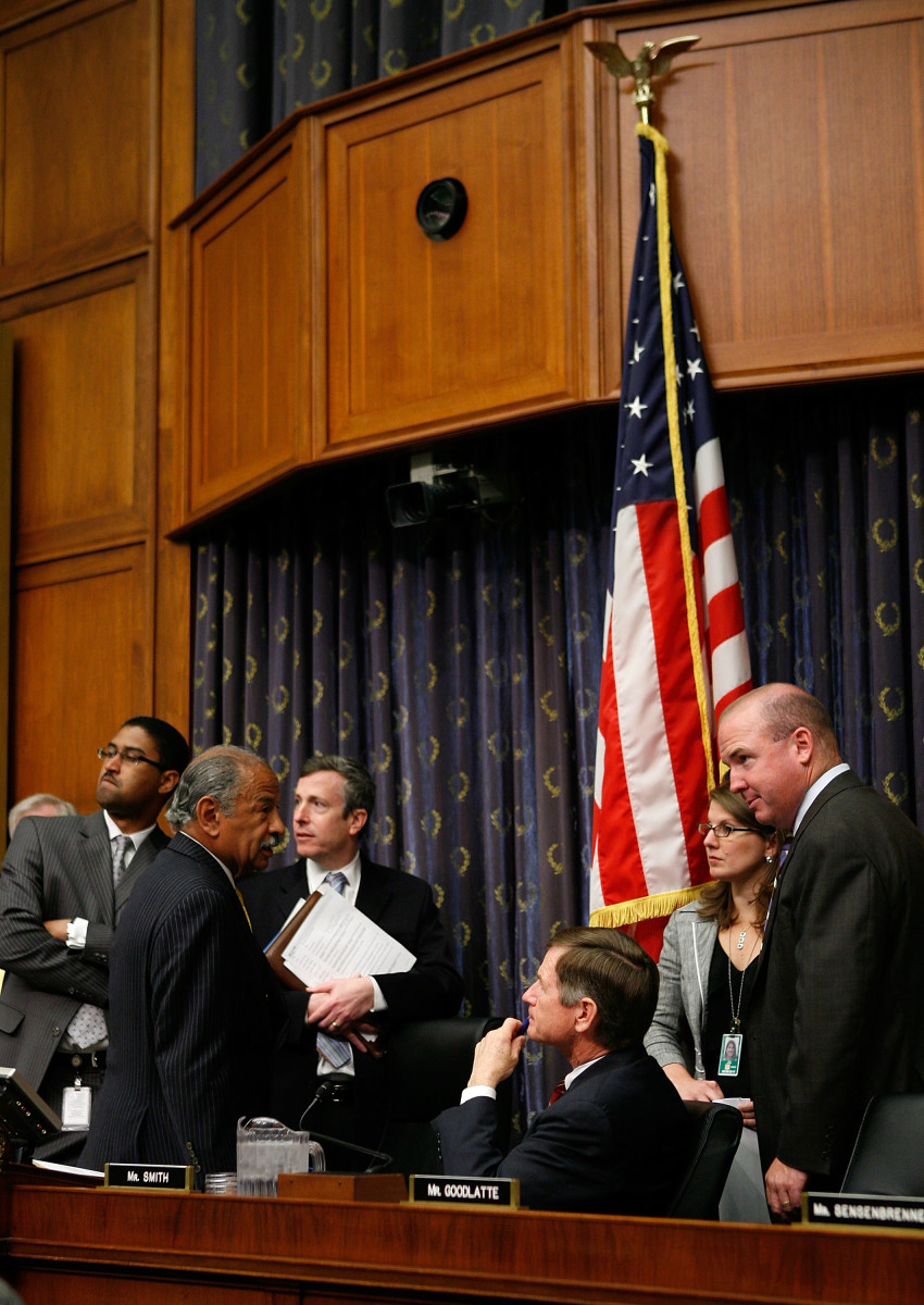 Representative John Conyers (D-Michigan) talks to Representative Lamar Smith (R-Texas) as aides listen prior to a hearing before the House Judiciary Committee on Capitol Hill on May 14th, 2009.