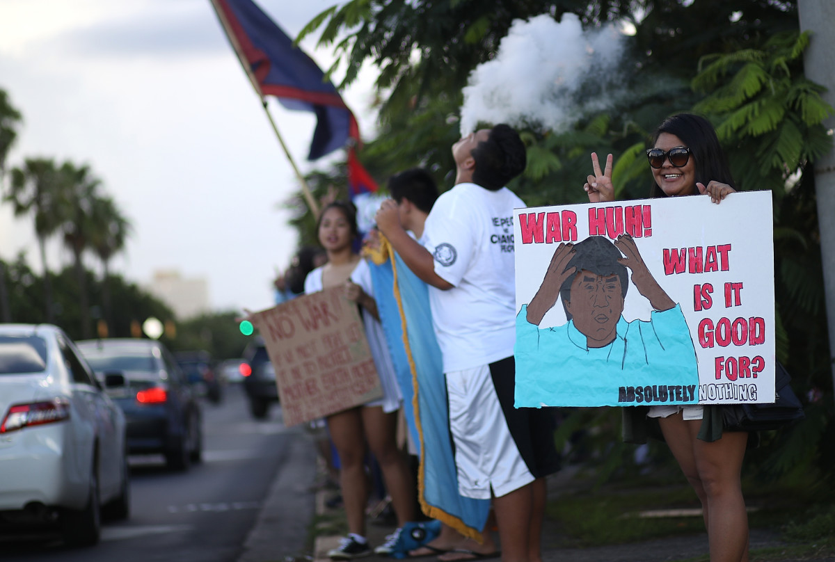 Protesters hold signs during a People for Peace Rally at the Chief Quipuha Statue on August 14th, 2017, in Hagatna, Guam.