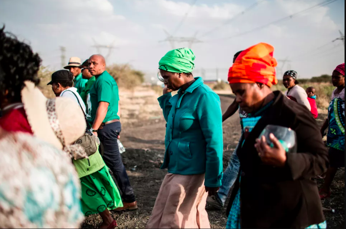 Widows of deceased striking miners who were killed during the Marikana massacre walk from the memorial site during the event's fifth anniversary in Marikana on August 16th, 2017. Thousands of South African miners sang remembrance songs at the site where police shot dead 34 strikers as campaigners demanded prosecutions and compensation. The 34 miners were gunned down after police were deployed to break up a wildcat strike that had turned violent at the Lonmin-owned Marikana platinum mine, northwest of Johannesburg.