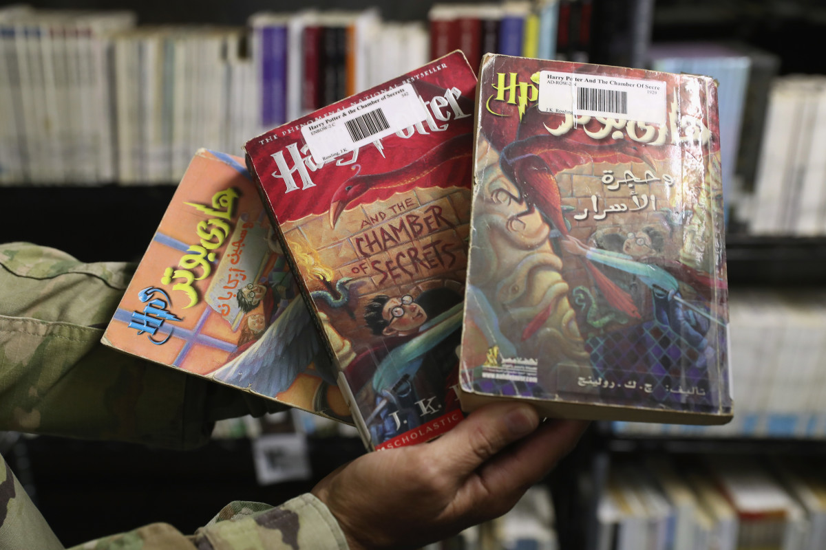 A military officer displays copies of Harry Potter books in Arabic and English at in the library of the Guantanamo Bay Detention Center on October 22nd, 2016.