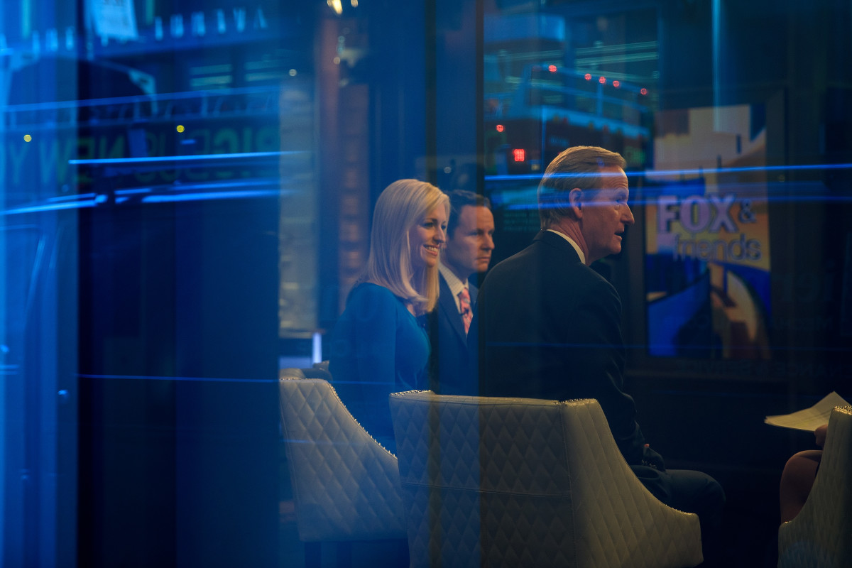 Seen through a window, (from left) hosts Ainsley Earhardt, Brian Kilmeade, and Steve Doocy broadcast Fox and Friends from the Fox News studios on February 17th, 2017, in New York City.