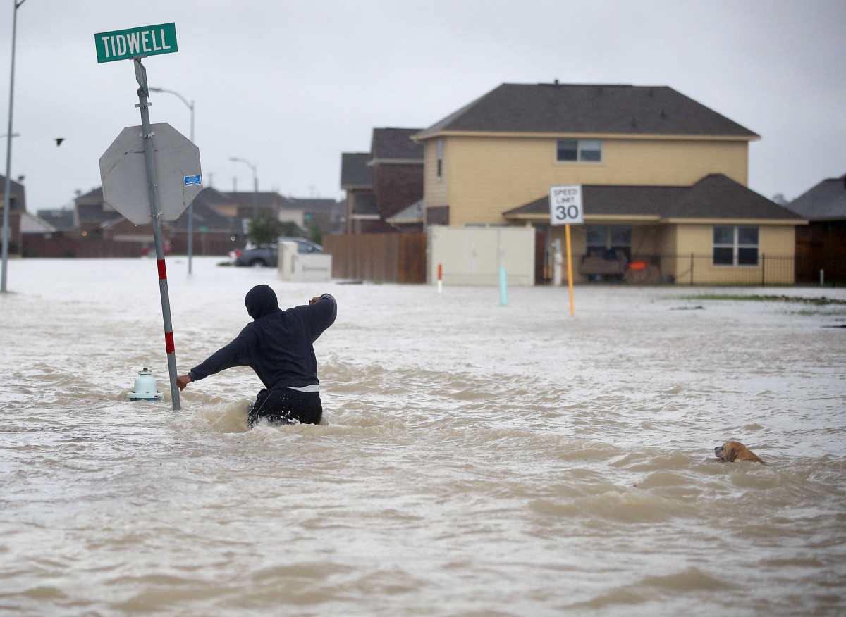 A person walks through a flooded street with a dog after the area was inundated with flooding from Hurricane Harvey on August 28th, 2017, in Houston, Texas.