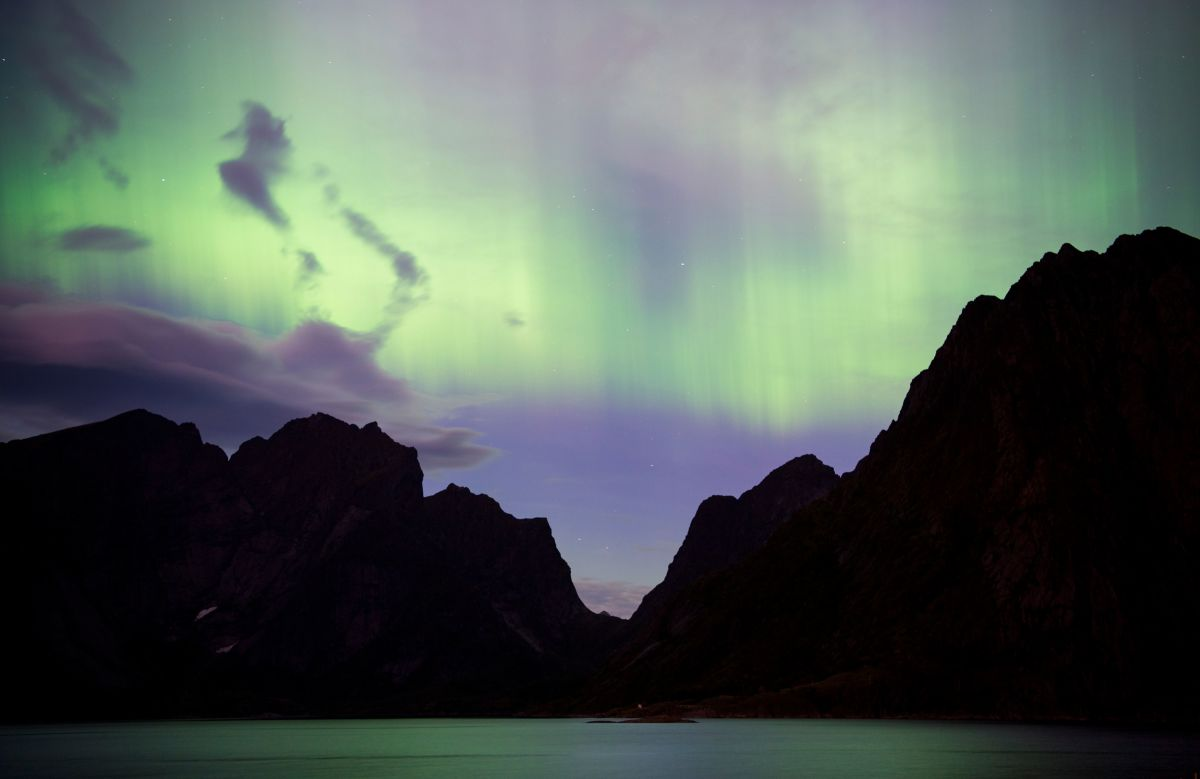 Northern lights (aurora borealis) illuminate the sky over Reinfjorden in Reine, on Lofoten Islands, Arctic Circle, on September 8th, 2017.