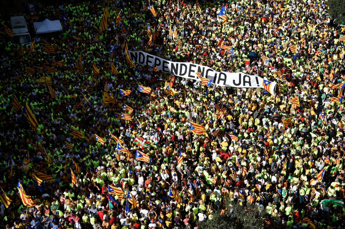 """People hold a banner reading """"Independence now!"""" in Catalan as they gather during a pro-independence demonstration, on September 11th, 2017, in Barcelona during the National Day of Catalonia. Hundreds of thousands of Catalans were expected to rally to demand their region break away from Spain in a show of strength three weeks ahead of a secession referendum banned by Madrid. The protest coincides with Catalonia's national day, the """"Diada,"""" which commemorates the fall of Barcelona in the War of the Spanish Succession in 1714 and the region's subsequent loss of institutions and freedoms."""