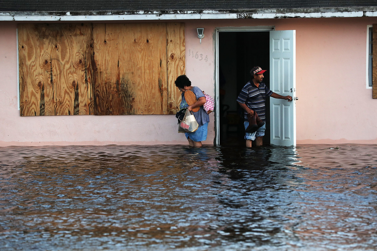 A couple leave their flooded home the morning after Hurricane Irma swept through the area on September 11th, 2017, in Fort Myers, Florida.