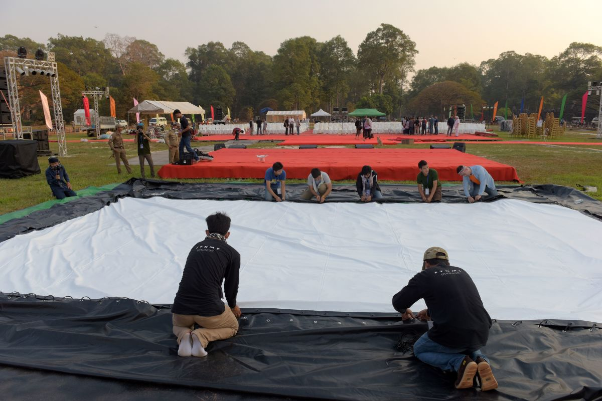 Cambodian workers help set up the area for the premiere.