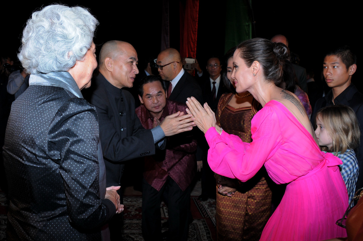 Angelina Jolie pays respect to Cambodian King Norodom Sihamoni as former queen Monique looks on during the premiere.