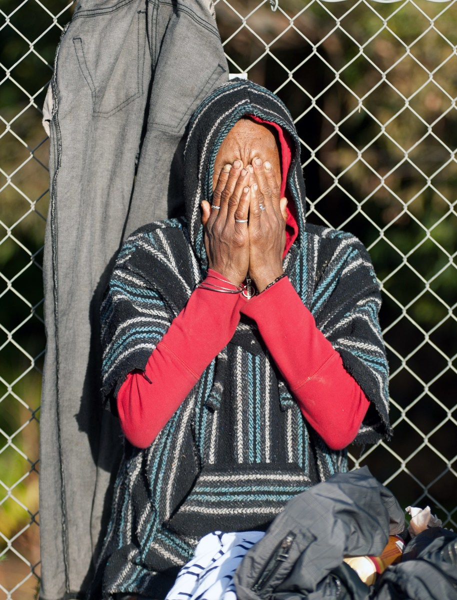"A displaced homeless person reacts as bulldozers move on a Silicon Valley homeless encampment known as ""The Jungle"" in San Jose, California. Authorities began dismantling the homeless camp in the heart of California's affluent Silicon Valley. The encampment is home to people forced out of an overheating rental market as lucrative tech companies have moved in in recent years."