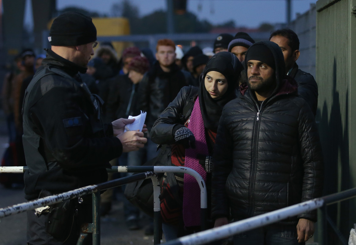 A German police officer directs migrants arriving from Austria at the border on October 17th, 2015, in Ering, Germany.