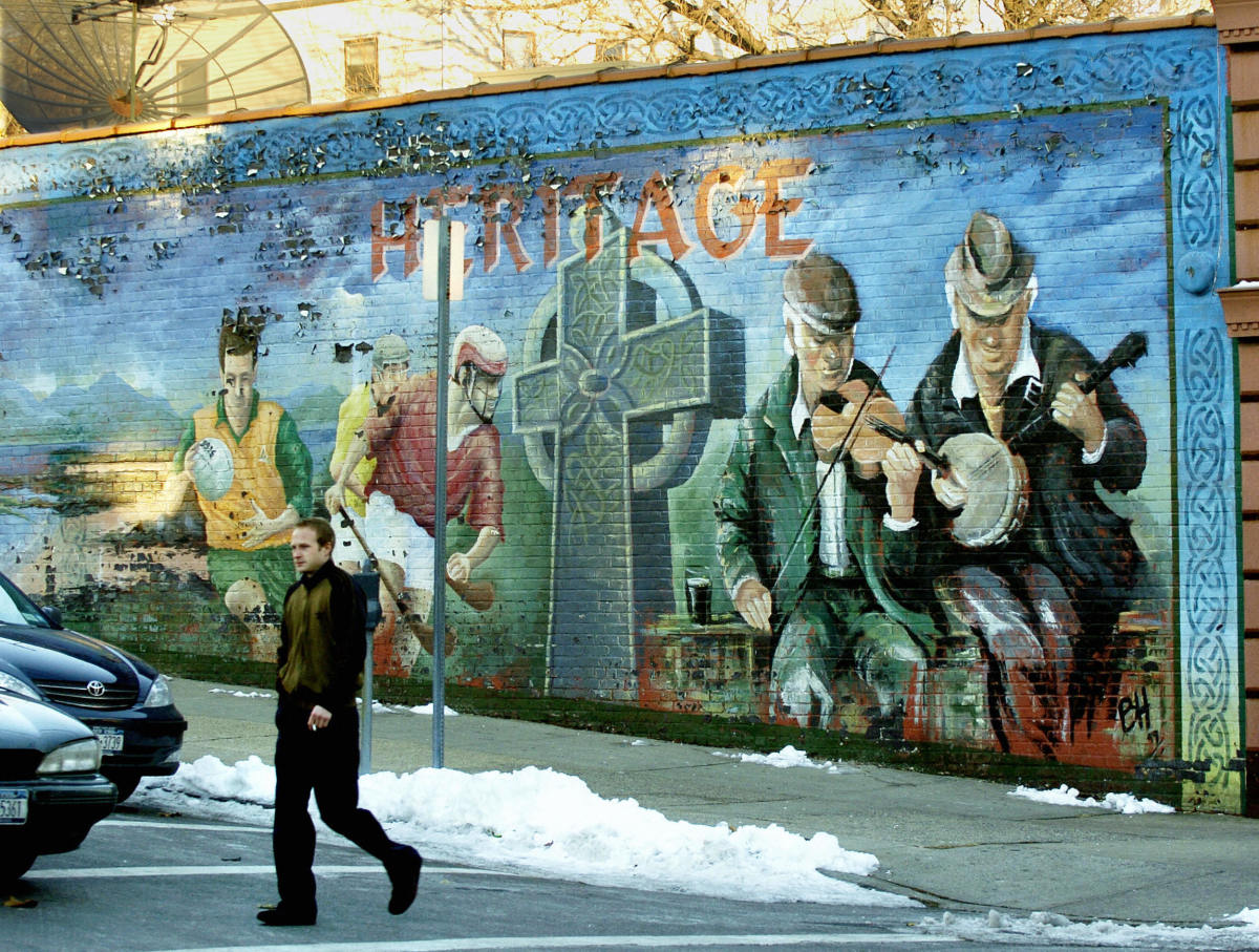 A man walks past a mural showing various scenes from Irish life in Yonkers, New York.