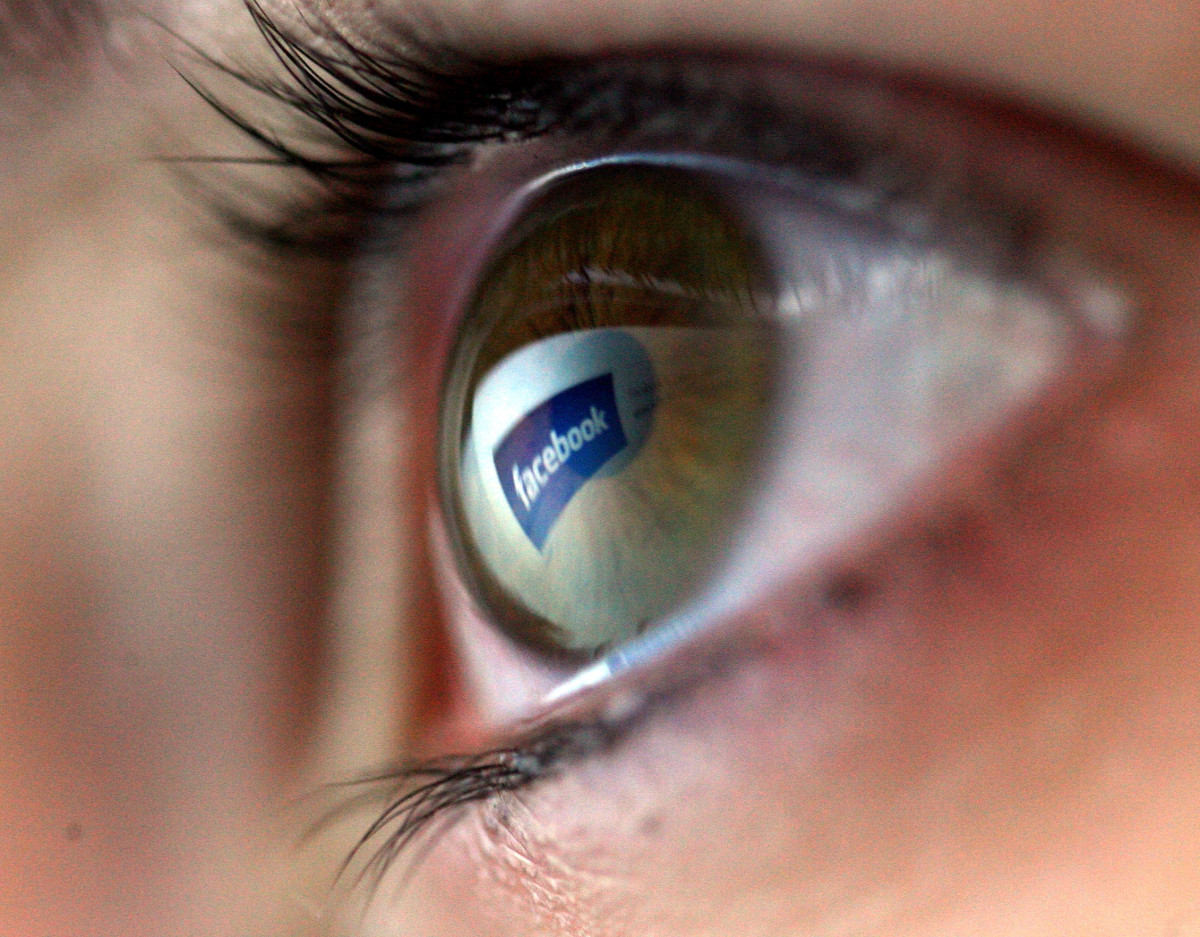 In this photo illustration the Facebook logo is reflected in the eye of a girl.