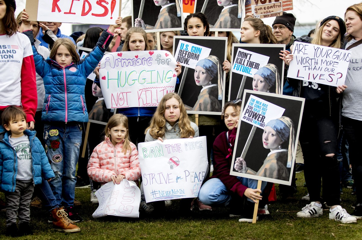 Young demonstrators hold signs during a rally calling for stronger gun control in the United States at the Museumsquare in the centre of Amsterdam on March 24th, 2018.