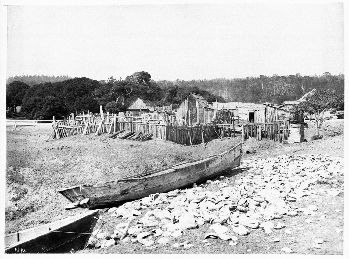 This photograph of a Chinese fishing village near Monterey, California, was taken around 1900. Discarded abalone shells litter the foreground next to two sampans—traditional boats used to forage the shoreline and transport the catch.
