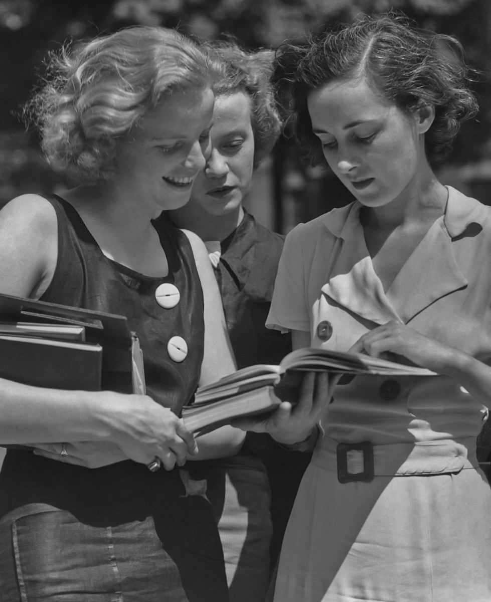 Three female students reading a book circa 1950.
