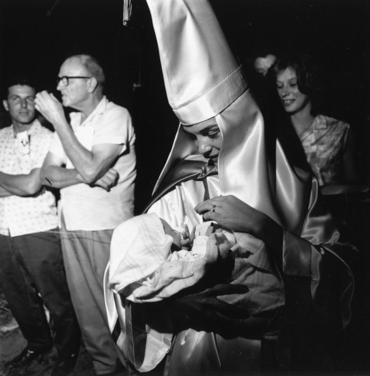 A woman wearing the robes and hood of the Ku Klux Klan holds her baby at a Klan meeting in Beaufort, South Carolina, on May 24th, 1965.