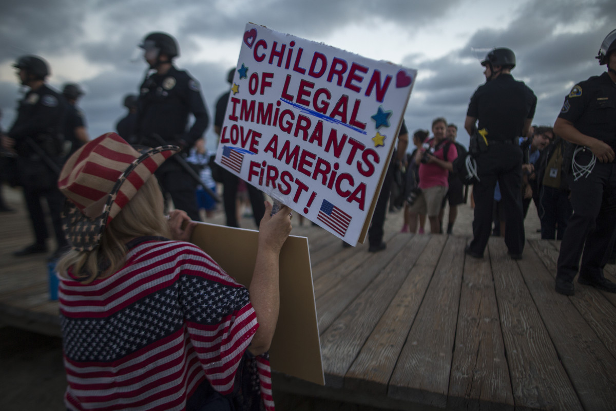 A demonstrator holds a sign during an America First rally on August 20th, 2017, in Laguna Beach, California.