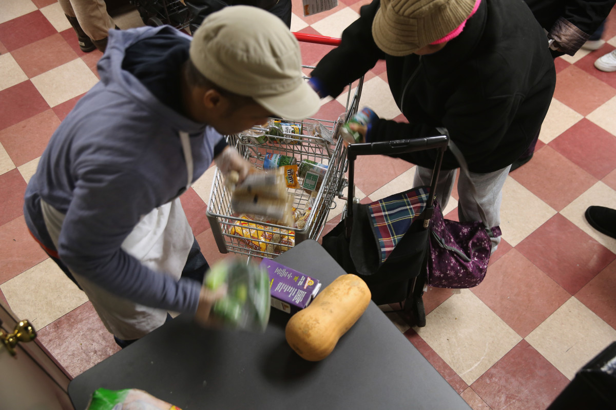 Harlem residents pack free groceries at the Food Bank For New York City on December 11th, 2013, in New York City.