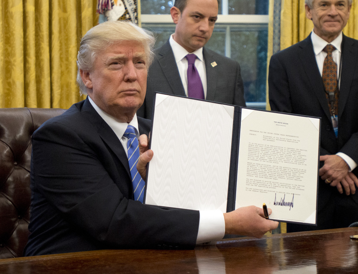 President Donald Trump shows the executive order withdrawing the U.S. from the Trans-Pacific Partnership after signing it in the Oval Office of the White House.