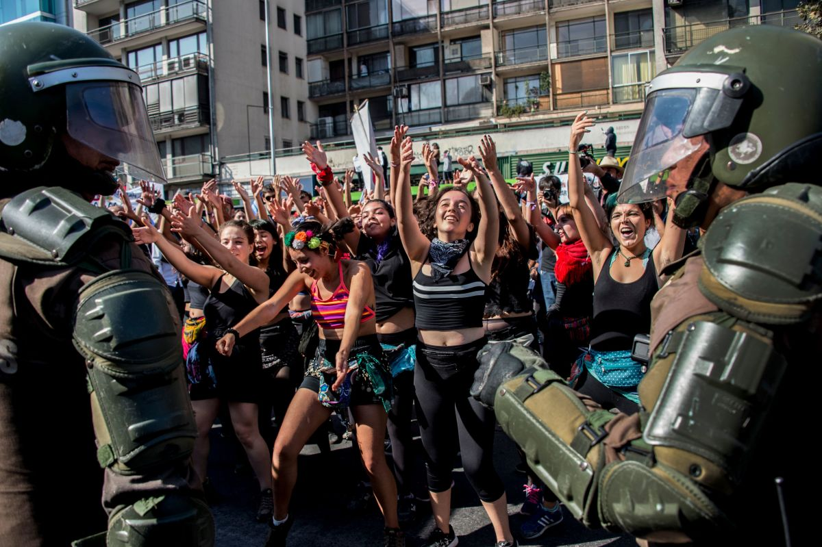 Students dance in front of riot police as they march to protest against the slowness in the progress of the Chilean education reform in Santiago on April 19th, 2018. Last month, Chile's constitutional court struck down a law that would have banned universities operating for profit, dealing a blow to free tuition reforms brought in by former leftwing president Michelle Bachelet. In a 6–4 decision, the court's judges sided with a group of private universities that challenged the measure as unconstitutional.