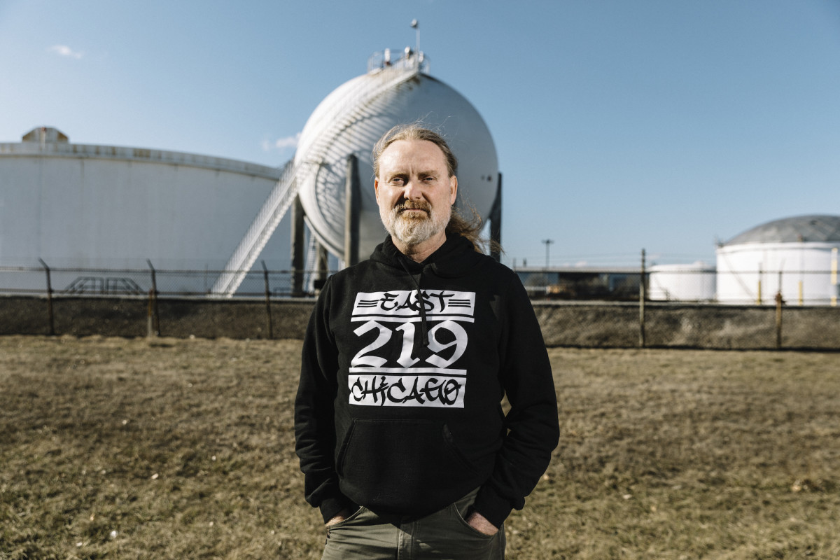 "Thomas Frank, a community activist who works with the East Chicago Community Strategy Group, stands in front of storage tanks on the Buckeye Pipeline property in the New Addition district of East Chicago. Frank describes the community group as an ""un-bought, un-bossed and an unparalleled community-driven group for Environmental Justice in East Chicago, Indiana, and the region."""