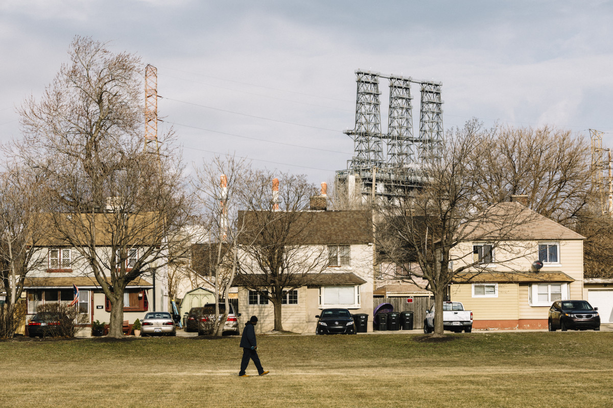 A man walks across a green space in Marktown, a historic district of East Chicago. The area is surrounded by heavy industry, including a new BP tar sands refinery.