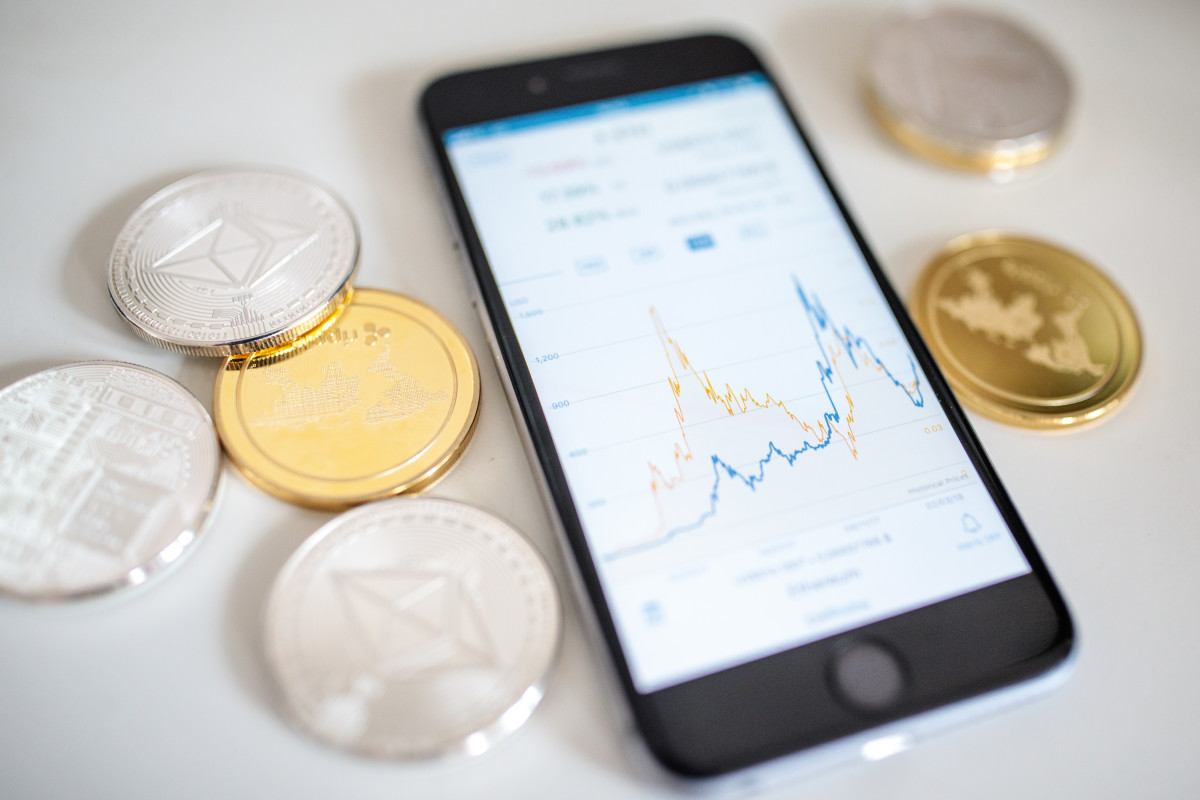 "In this photo illustration of the litecoin, ripple and ethereum cryptocurrency ""altcoins"" sit arranged for a photograph beside a smartphone displaying the current price chart for ethereum on April 25th, 2018, in London, England. Cryptocurrency markets began to recover this month following a massive crash during the first quarter of 2018, seeing more than $550 billion wiped from the total market capitalization."