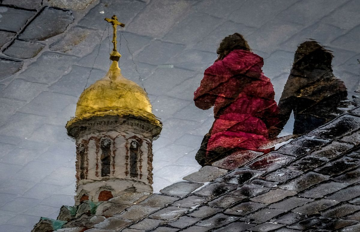 Women are reflected in a puddle as they walk across the Red Square in Moscow on April 26th, 2018.