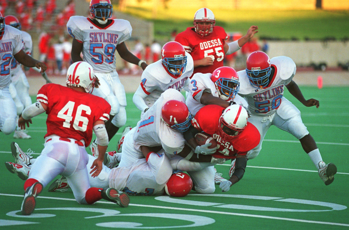Football players from Odessa High School and Dallas Skyline High School play on September 1st, 2000, in Odessa, Texas.