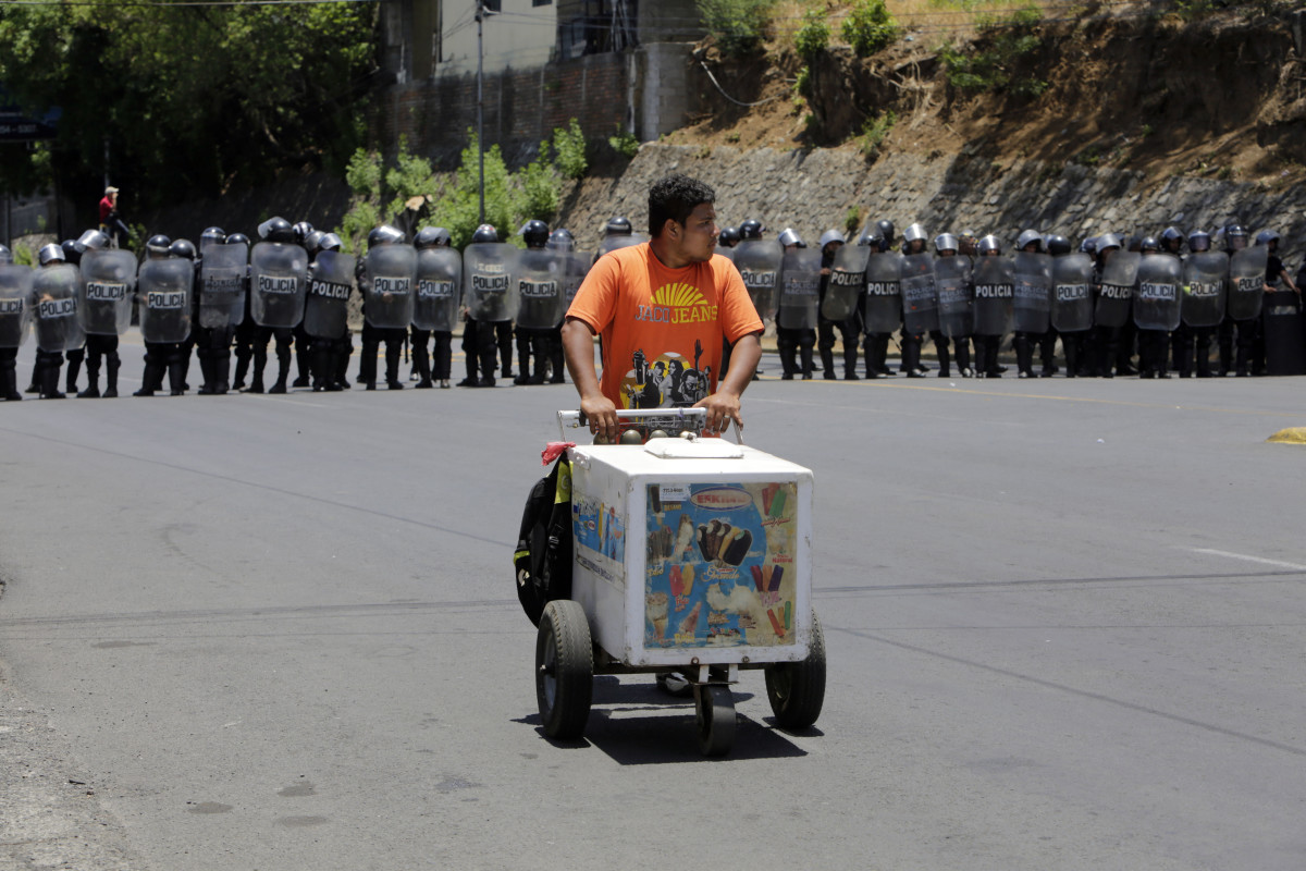 An ice-cream salesman walks in front of riot police agents blocking the road as demonstrators protest during a march to the National Congress to demand justice for the 43 deaths in recent protests in Managua on May 2nd, 2018.