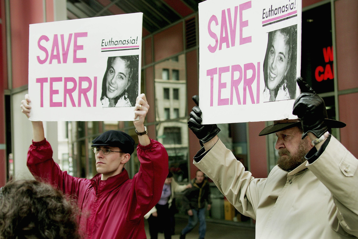 John Jansen and Joseph Scheidler carry signs calling for continued care and feeding of Terry Schiavo during a protest at the Thompson Center Plaza on March 29th, 2005, in Chicago, Illinois.