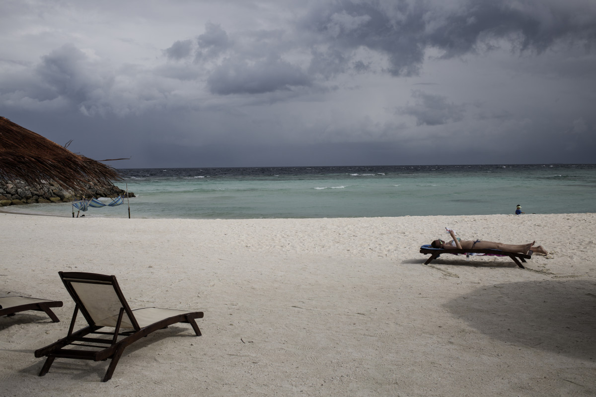 Tourists relax on the beach with rain on the horizon on in Maafushi, Maldives. A new study attributes the vast majority of the Maldives' emissions to tourism.