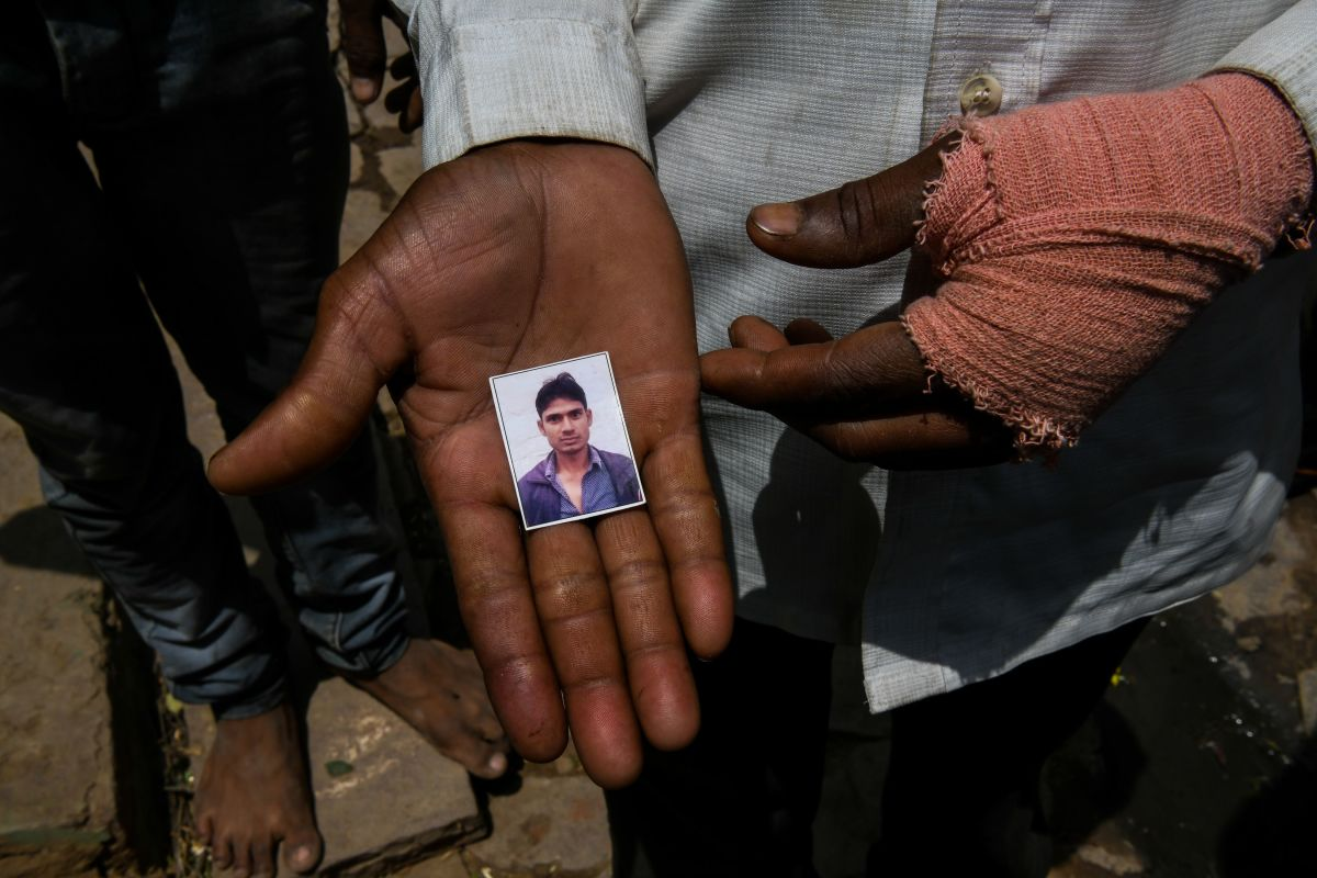A man shows a photo of Gautam Singh, 26, who died with 24-year-old Sunil Kumar after getting crushed under the debris of a ceiling that fell in heavy storm winds in Kheragarh on the outskirts of Agra on May 4th, 2018.
