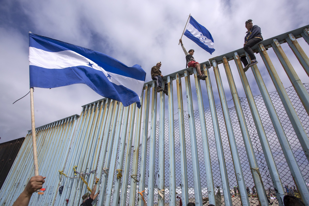 People hold Honduran flags at the border fence during a rally with members of a caravan of Central American asylum seekers and supporters on April 29th, 2018, in Tijuana, Mexico.