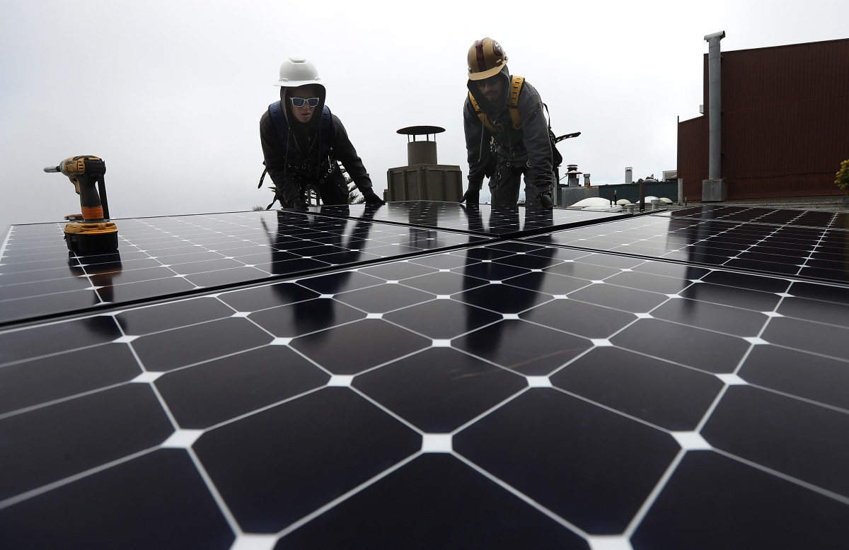Workers install solar panels on the roof of a home on May 9th, 2018, in San Francisco, California.