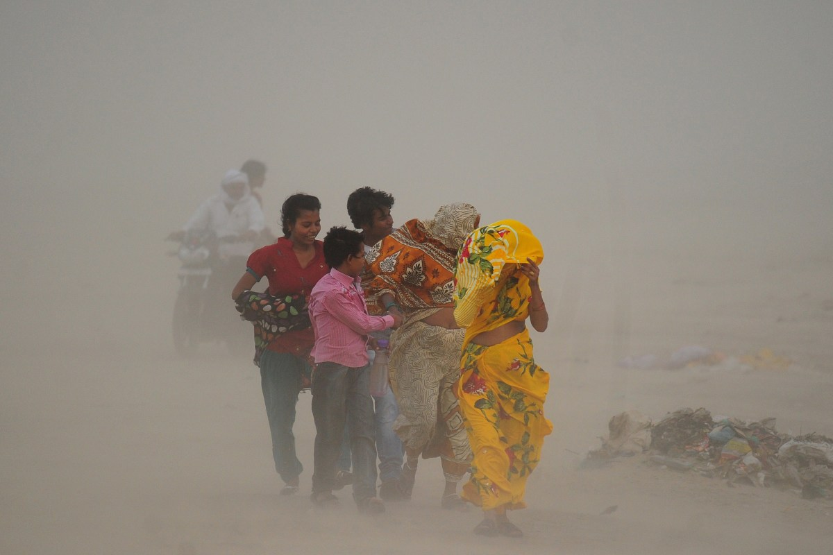 Indian Hindu devotees walk through a dust storm at the Sangam.