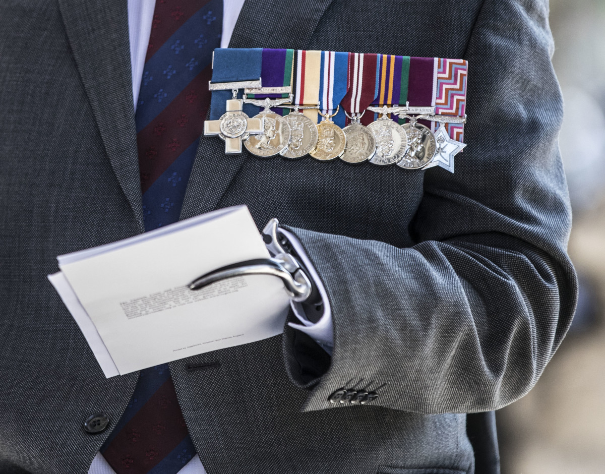 Major Peter Norton GC grips a program in his prosthetic hand as he waits to greet Prince Charles, Prince of Wales (not seen) at the door as he attends the bi-annual service of the Victoria Cross and George Cross Association at St Martin-in-the-Fields on May 15th, 2018, in London, England. Major Norton lost an arm and a leg while leading an EOD team in Iraq in 2005.