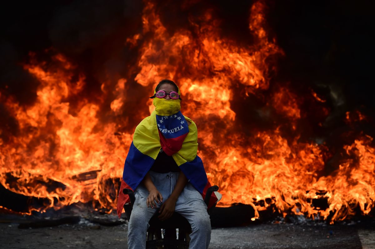 A Venezuelan opposition activist is backdropped by a burning barricade during a demonstration against President Nicolas Maduro in Caracas, on April 24th, 2017. Protesters rallied on Monday vowing to block Venezuela's main roads to raise pressure on Maduro after three weeks of deadly unrest that have left 21 people dead. Riot police fired rubber bullets and tear gas to break up one of the first rallies in eastern Caracas early Monday while other groups were gathering elsewhere, the opposition said.