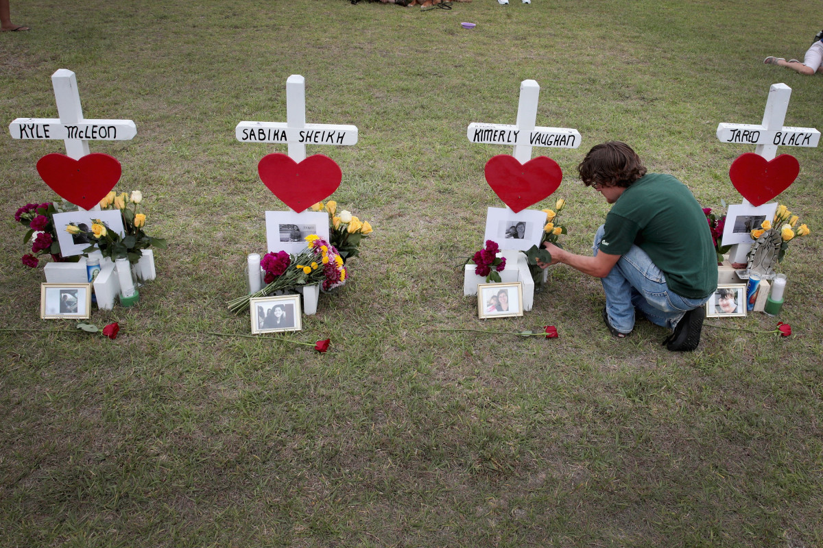 James Otto, a 2011 graduate of Santa Fe High School, leaves flowers at a memorial in front of the school on May 21st, 2018, in Santa Fe, Texas.