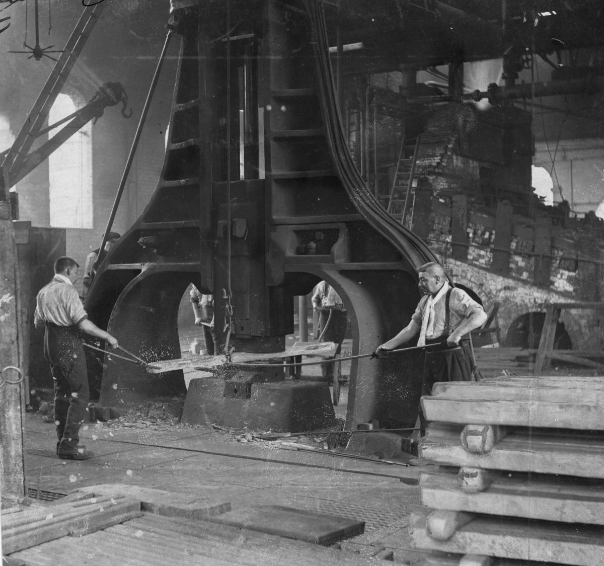 Steel workers in Pittsburgh, Pennsylvania, where the Bessemer Converter was in use manhandling a piece of hot steel.