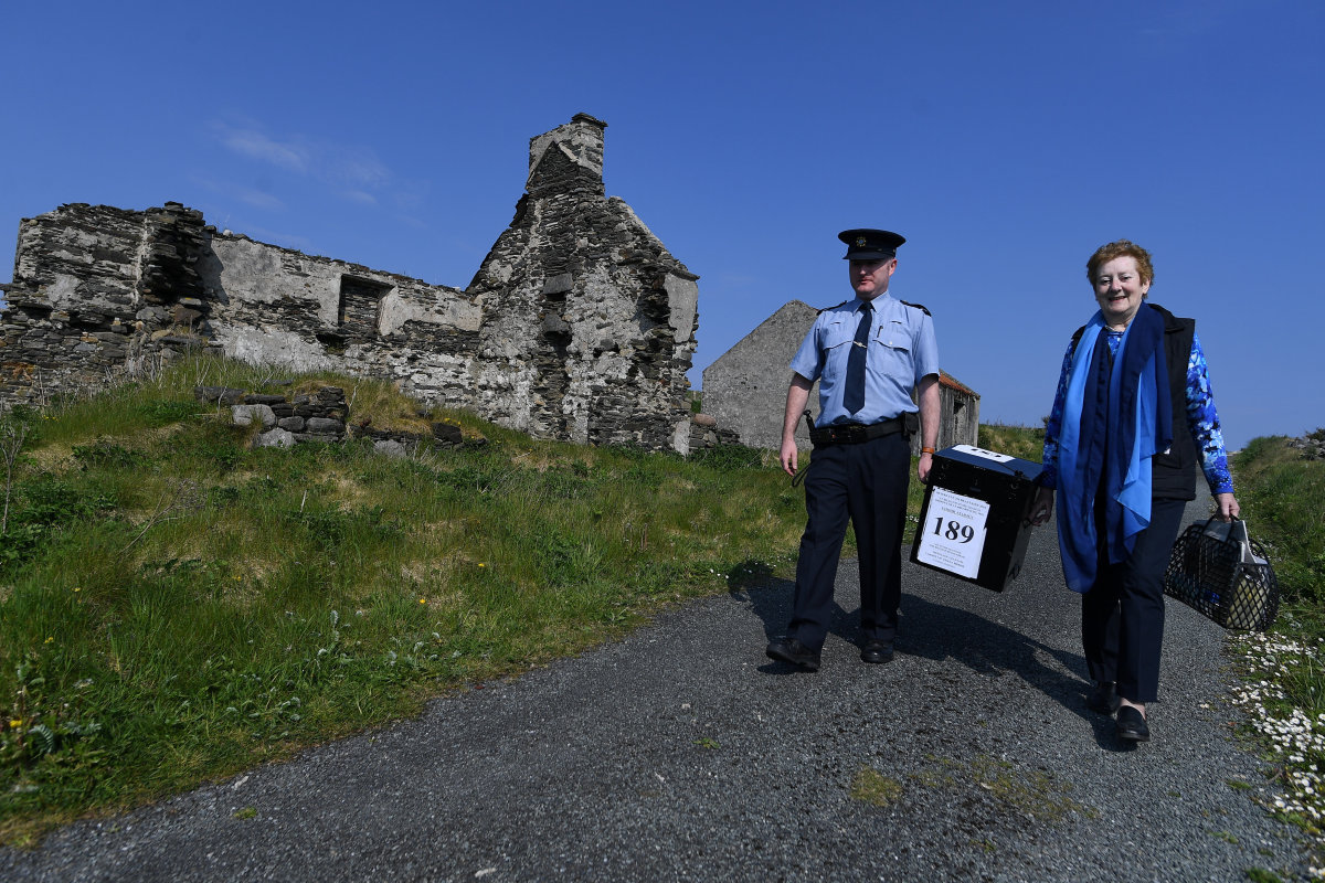 Presiding Officer Carmel McBride and Garda Alan Gallagher carry the polling box for the referendum on liberalizing abortion law a day early onto the Donegal coastal island of Inishbofin, Ireland, on May 24th, 2018.