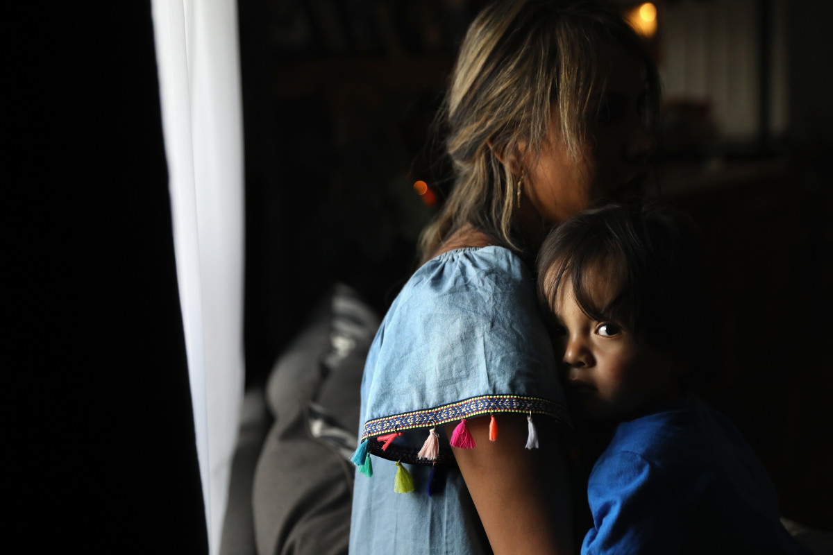 An undocumented woman from Peru holds her one-year-old son at their home in Thornton, Colorado.