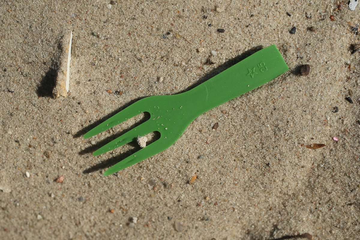 A plastic fork lies on a beach along the Spree River in the city center on May 29th, 2018, in Berlin, Germany. Europe is struggling to combat plastics pollution in its waterways and seas. It recently announced it will seek to ban the use of certain common plastic items, including plastic cutlery, straws, plates, swabs, and fishing gear.