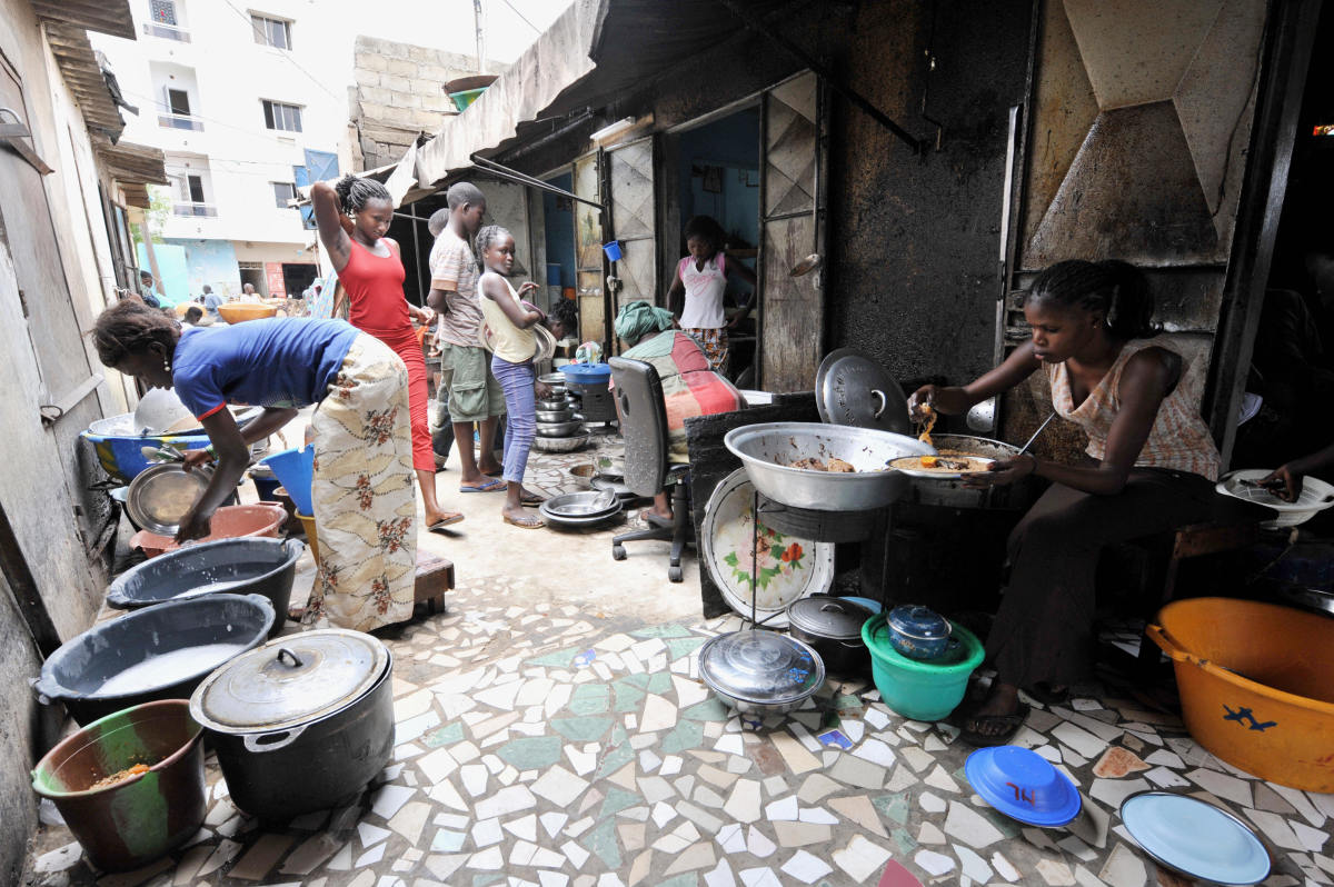 A woman prepares rice and fish at her street restaurant in Dakar, Senegal.