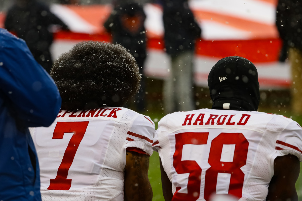 Colin Kaepernick and Eli Harold of the San Francisco 49ers kneel for the national anthem at Soldier Field in Chicago, Illinois, on December 4th, 2016.
