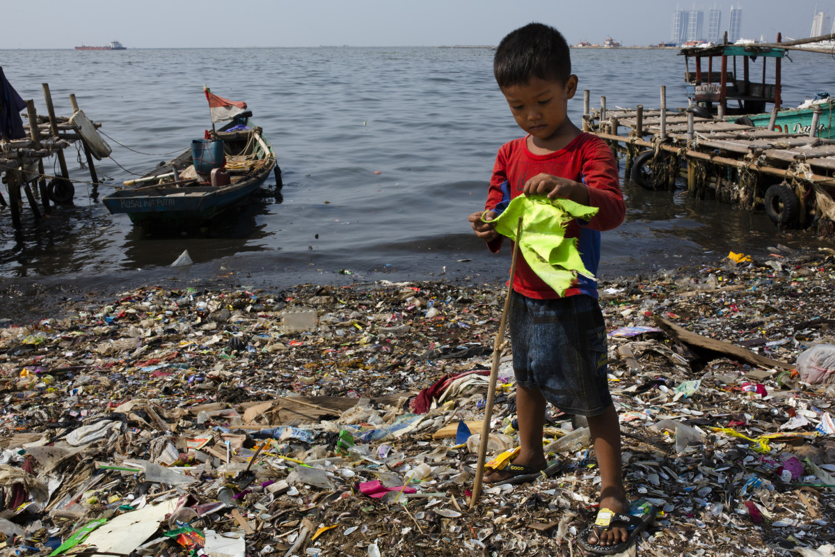 A boy plays with a makeshift flagpole on a beach covered in plastic waste at a fishing village on the northern coast on May 31st, 2018, in Jakarta, Indonesia. Indonesia has been ranked the second biggest marine polluter in the world behind only China, with reports showing that the country produces 187.2 million tons of plastic waste each year.