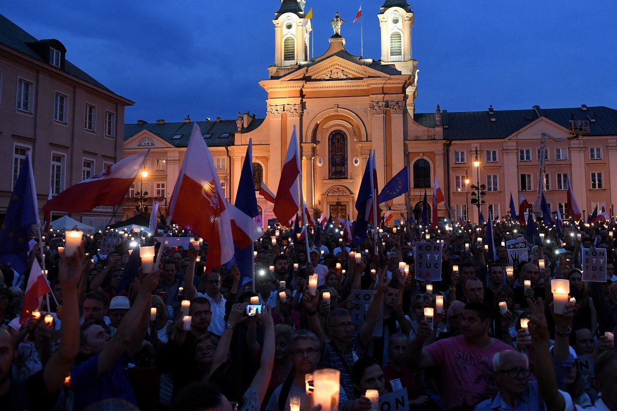 People hold candles and Polish national flags as they take part in a demonstration in front of the Polish Supreme Court on July 23rd, 2017, in Warsaw, Poland.