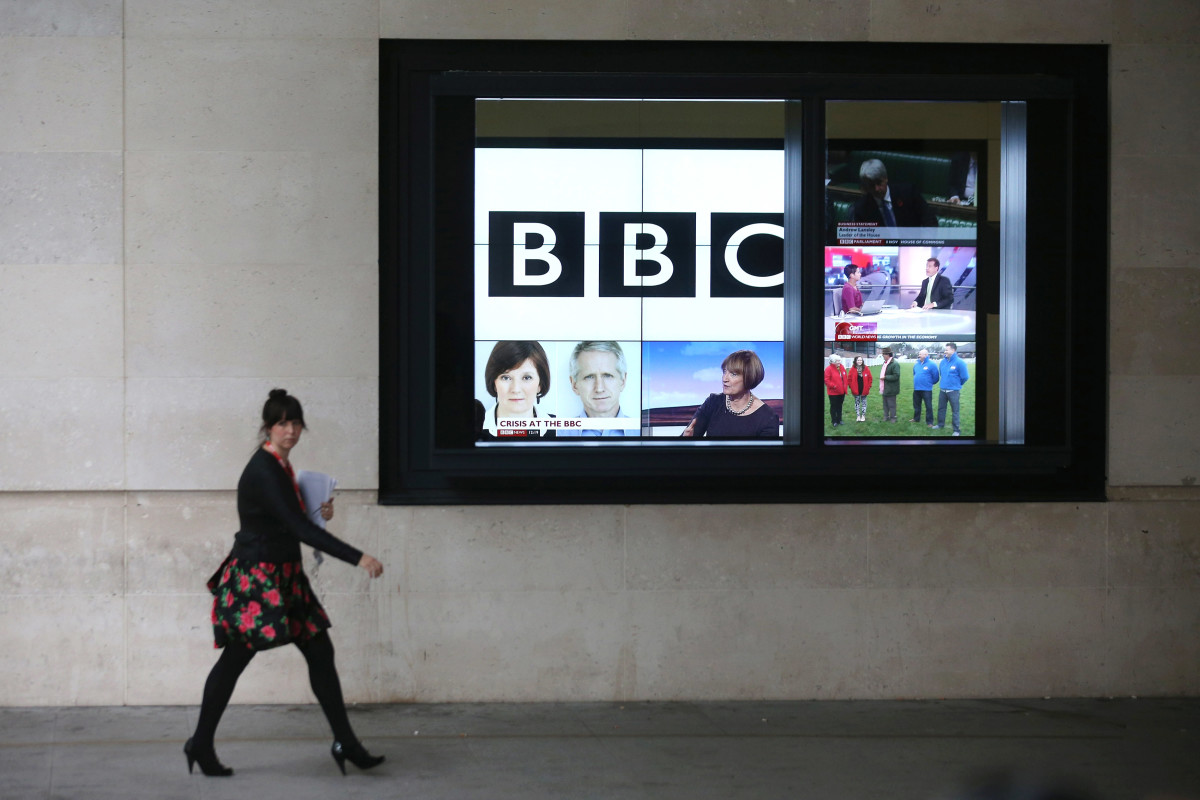 A woman walks past a bank of television screens displaying BBC channels in the BBC headquarters on November 12th, 2012, in London, England.