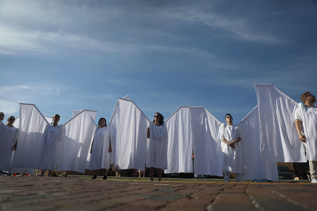 People dressed as angels stand in front of the memorial set up for the shooting victims at Pulse nightclub on June 12th, 2018, where the shootings took place two years ago in Orlando, Florida.
