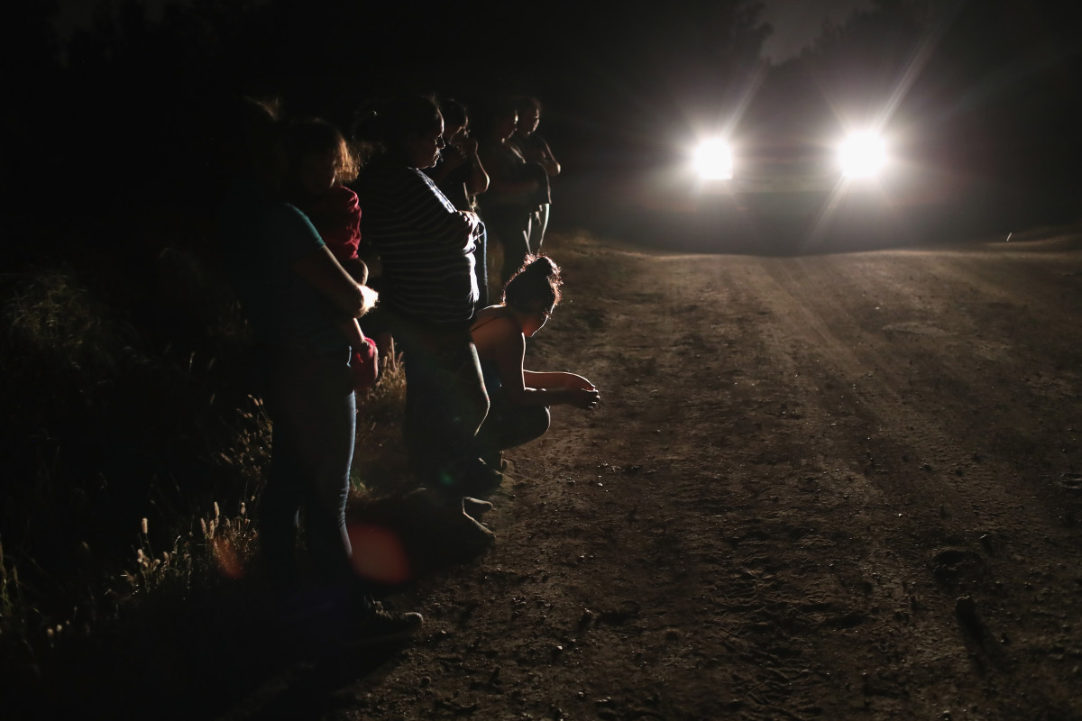 Central American asylum seekers wait for transport while being detained by U.S. Border Patrol agents near the U.S.-Mexico border on June 12th, 2018, in McAllen, Texas. The group of women and children had rafted across the Rio Grande from Mexico and were detained before being sent to a processing center for possible separation.