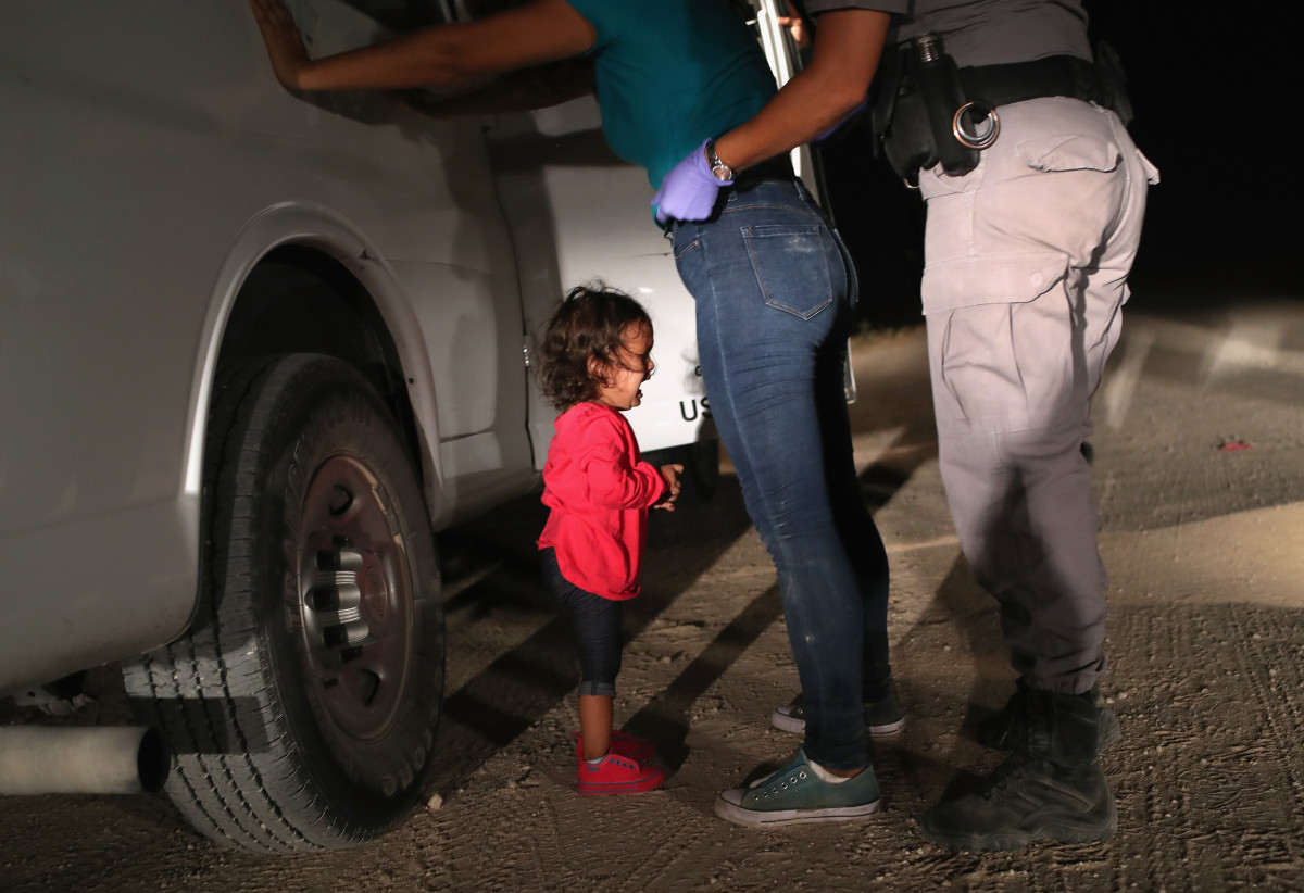 A two-year-old Honduran asylum seeker cries as her mother is searched and detained near the U.S.-Mexico border on June 12th, 2018, in McAllen, Texas. The asylum seekers had rafted across the Rio Grande from Mexico and were detained by Border Patrol agents before being sent to a processing center for possible separation.